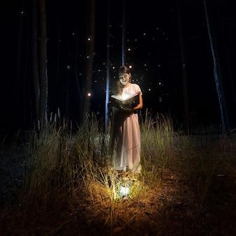 Bella donna in abito lungo che legge un grande vecchio libro nella foresta misteriosa con le lucciole