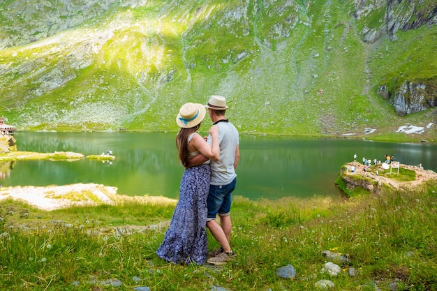 Una bella donna in un abito lungo e un cappello di paglia abbraccia con l'uomo vicino al lago balea nelle montagne rumene.