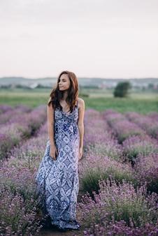 Bella donna in un abito lungo a piedi in un campo di lavanda al tramonto.