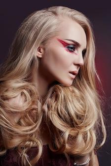 Colorazione capelli lunghi bella donna in ultra biondo, trucco naturale. riccioli di acconciatura alla moda fatti in un salone di bellezza. ragazza bionda di moda