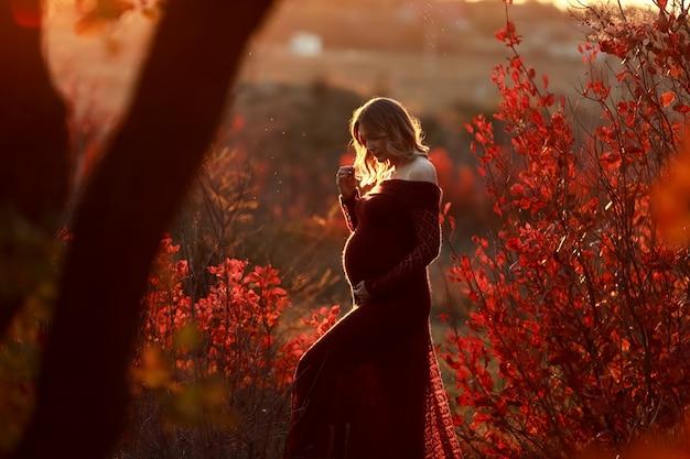 Bella donna in un lungo abito rosso sotto i raggi del tramonto nella foresta d'autunno