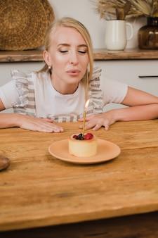 Una bella donna guarda una torta con una candela e gioisce. concetto di compleanno