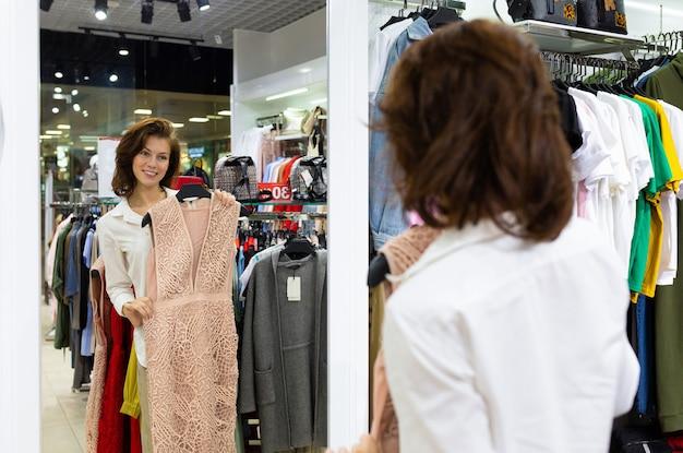 Una bella donna guarda un lungo abito estivo in polvere con una profonda scollatura allo specchio.