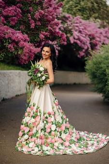 Bella donna in un abito lussuoso è in piedi in un giardino fiorito di lillà