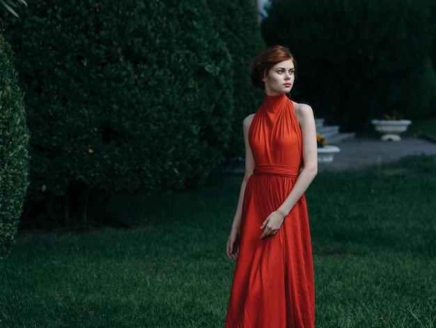 Bella donna sul parco vestito rosso sguardo attraente di lusso. foto di alta qualità