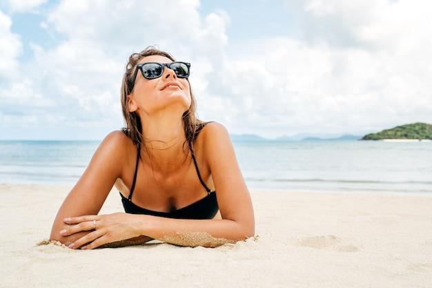 Bella donna sdraiata sulla sabbia della spiaggia