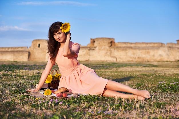 Bella donna sdraiata sull'erba. picnic contro il castello medievale