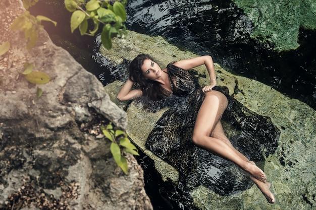 Bella donna che si trova sulle pietre in acqua