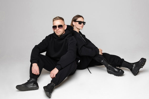 Bella donna e uomo in abiti neri seduti schiena contro schiena e sorridente. occhiali da sole sui loro volti