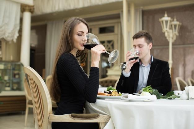 Bella donna e uomo che bevono vino al ristorante