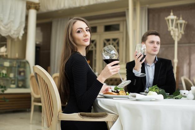 Bella donna e uomo al ristorante, con in mano un bicchiere di vino