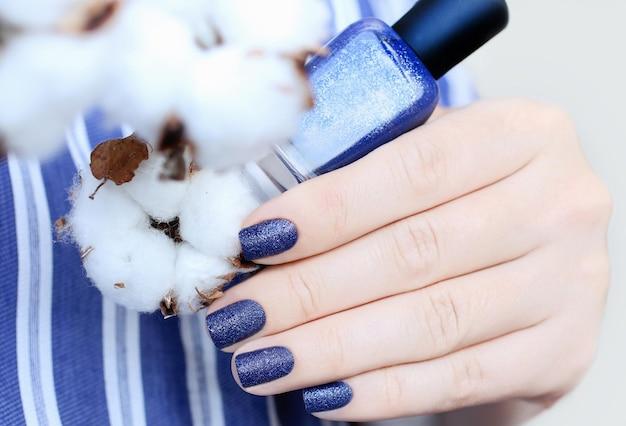 Bella donna manicureclasse tonalità di blusand textured manicurela donna mostra le sue unghie
