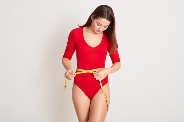 Bella donna che misura la sua vita tramite nastro giallo misura, femmina magra che indossa un abito rosso combinato, perde peso, ha i capelli lisci scuri, in posa contro il muro bianco. concetto di fitness e dieta