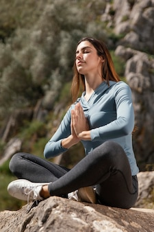 Bella donna che medita all'aperto