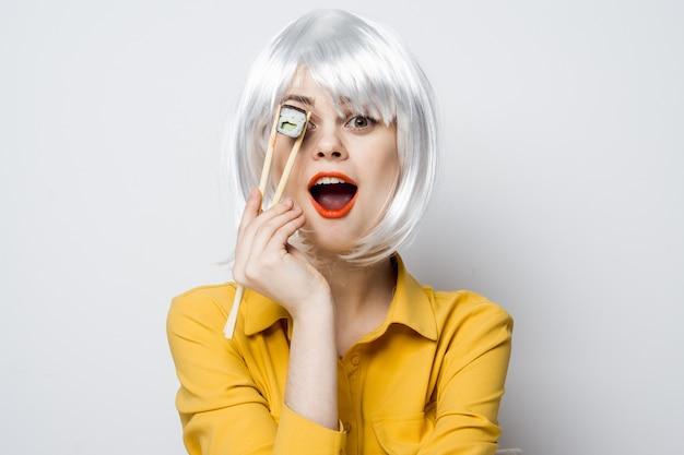 Modello di bella donna che mangia sushi e panini dalla consegna del cibo al tavolo in una camicia gialla che propone emozioni diverse