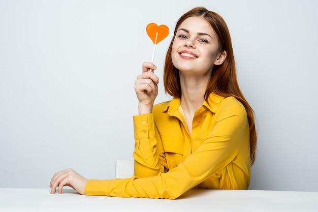 Modello di bella donna con un lecca-lecca di cuore al tavolo in una camicia gialla emozioni di san valentino