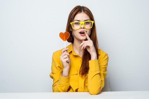 Modello di bella donna con una lecca-lecca cuore al tavolo in una camicia gialla pone diverse emozioni. san valentino