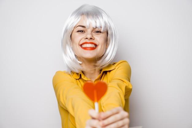 Modello di bella donna con un lecca-lecca di cuore al tavolo in una camicia gialla pone emozioni diverse. san valentino