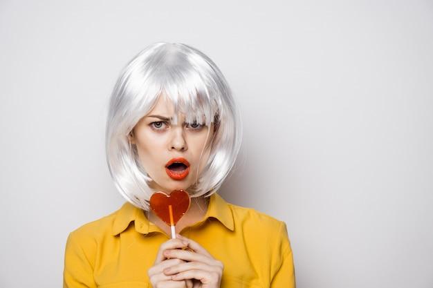 Modello di bella donna con una lecca-lecca cuore al tavolo in una camicia gialla pone diverse emozioni.