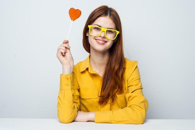 Modello di bella donna con una lecca-lecca cuore al tavolo in una camicia gialla pone. san valentino