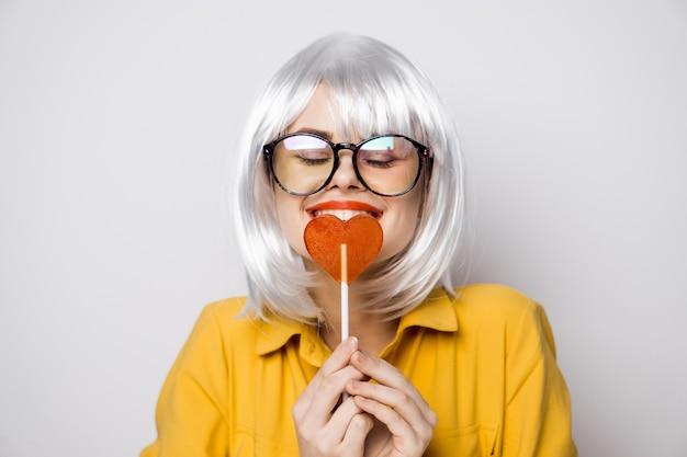Modello di bella donna con un lecca-lecca di cuore in una parrucca bianca di san valentino della camicia gialla