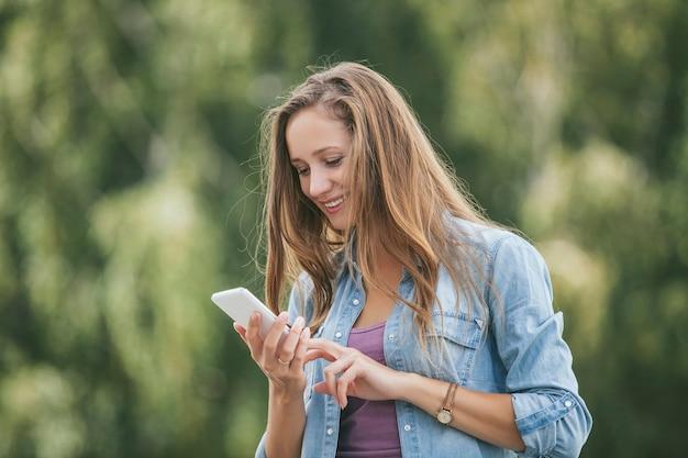 Modello di bella donna con smartphone cellulare all'esterno