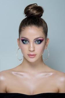 Modello di bella donna con trucco professionale in un abito da sera nero e grandi orecchini nelle orecchie