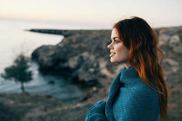 Bella donna in montagna con un plaid sulle spalle vicino al modello dell'albero del mare