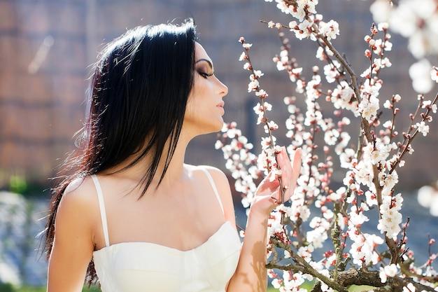 Bella donna vicino all'albero in fiore caratteristica stagionale bellezza e moda