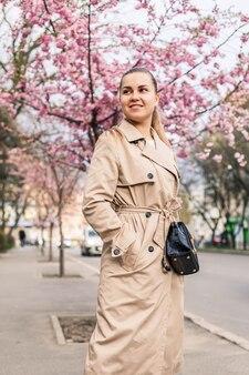 Bella donna vicino agli alberi di sakura. i fiori rosa sbocciano sugli alberi in una strada cittadina. gli alberi fioriscono intorno. concetto di primavera