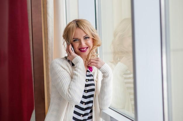 Bella donna vicino alla finestra utilizzando il telefono