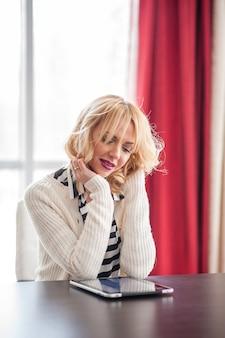 Bella donna vicino alla finestra utilizzando tablet