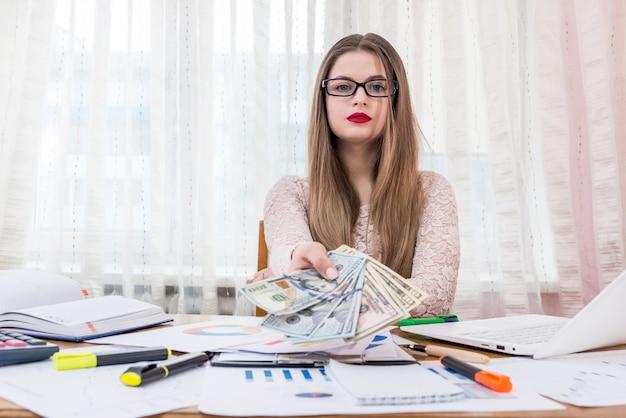 Bella donna, impiegato, offrendo banconote in dollari