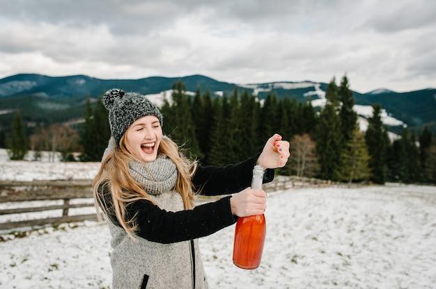 Bella donna apre una bottiglia di champagne contro le montagne invernali.