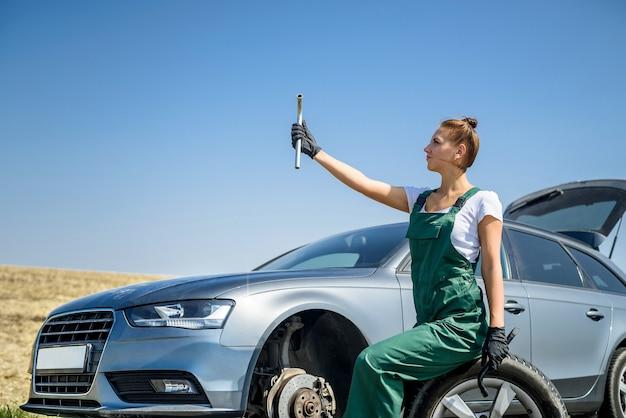 Bella donna in tuta con le chiavi che ripara un'auto rotta nel suo viaggio