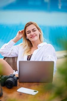 Bella donna fotografo blogger in vacanza, lavorando con il computer portatile in piscina. lavoro a distanza freelance