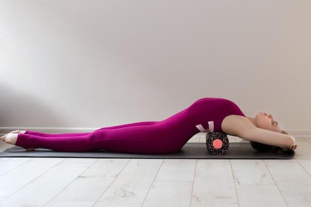 Bella donna istruttore di pilates stretching e riscaldamento utilizzando il rullo di schiuma, lavorando, indossando abbigliamento sportivo rosa, primo piano. sport e concetto di stile di vita attivo sano.