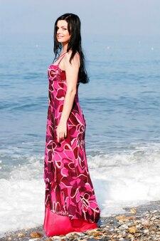 Bella donna in abito rosa sulla spiaggia del mare