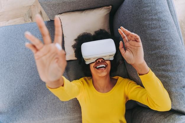 Bella donna che gioca a casa con l'auricolare vr - donna nera sdraiata sul divano mentre interagisce con la tecnologia della realtà aumentata augment