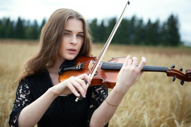 Bella donna che suona il violino nel campo di grano