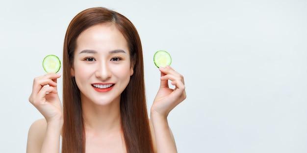 Bella donna che gioca con fette di cetriolo e sorride, migliorando la levigatezza della pelle