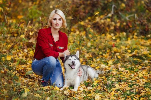 Bella donna gioca con il cane husky nella foresta di autunno