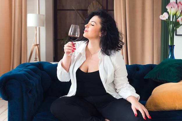 Bella donna plus size rilassarsi con un bicchiere di vino