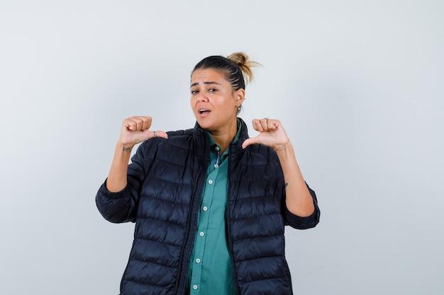 Bella donna che indica se stessa con i pollici in camicia verde, giacca nera e sembra carina, vista frontale.