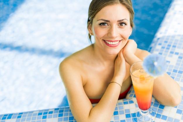 Bella donna in una piscina con un cocktail accanto a lei