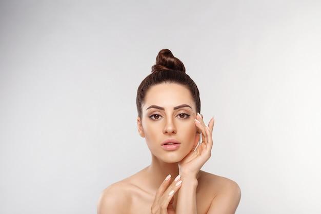 Ritratto di bella donna, concetto di cura della pelle, bella pelle. ritratto di mani femminili con unghie manicure.