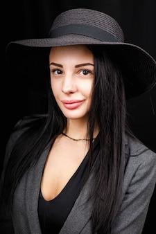 Ritratto di bella donna con un grande cappello. look vintage. trucco alla moda. il cappello copre metà del viso.