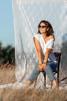Bella donna in posa sullo sfondo di tende bianche in un campo di fiori