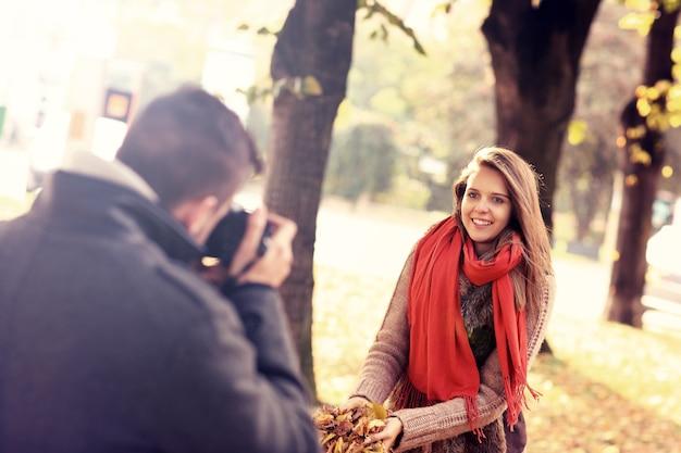 Una bella donna in posa davanti alla telecamera nel parco in autunno