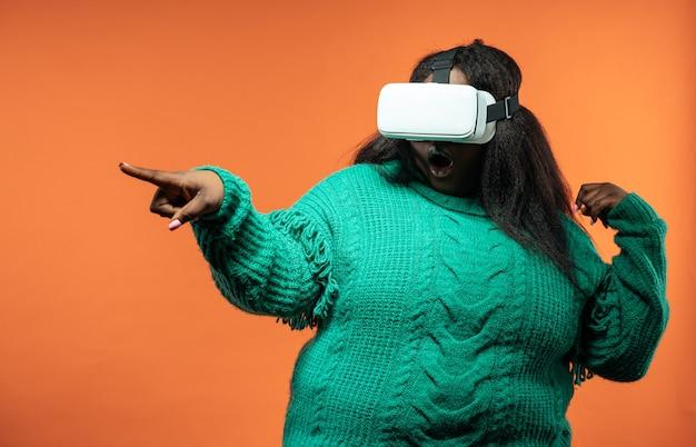 Bella donna in posa in abiti casual su uno sfondo colorato utilizzando la realtà virtuale visiera
